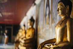 Budha statue close-up with others blurred in the background. Royalty Free Stock Images