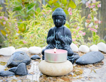 Budha Water Garden. Figure of Buddha praying in a small zen pond with stones and a garden at the background Royalty Free Stock Images