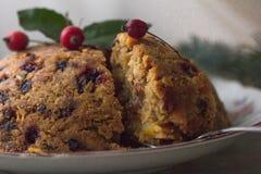 Budino inglese di natale con il cucchiaio Budino cotto al vapore inglese tradizionale con i frutti secchi e dadi per il Natale su fotografia stock libera da diritti