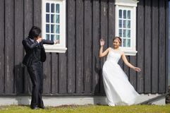 Unidentified bride and groom posing in front of Famous black church,Iceland. Royalty Free Stock Images