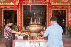 Budistas que se encienden encima de velas y de palillos de ídolo chino en templo chino Imágenes de archivo libres de regalías
