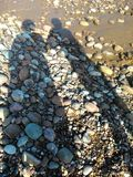Budleigh Pebble Beach Photograph with Shadows of Two People. A photo of Budleigh Salterton pebble beach with two long shadows of a large and thin person stock photo