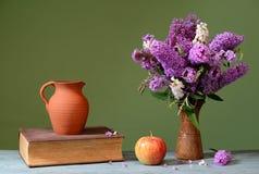 Budleja em um vaso, em uma maçã e em uns livros cerâmicos Foto de Stock