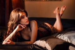 Budoarfoto av den sexiga flickan som bär den stilfulla underkläderna som poserar i sovrummet Härlig näck sexig brunettkvinna i sv arkivfoton