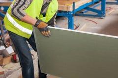 Budować ścianę dla ramowego domu Pracownik trzyma drywall Obrazy Stock