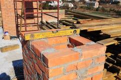 Budować ceglanego komin Kamieniarstwo Kominowa budowa - cegła Kłaść narzędzie Spirytusowego poziom Obrazy Stock