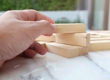 Budować drewnianą blokową łamigłówkę na stole, kopii przestrzeni i zbliżenie ręce marmurowych/próba budować bloków drewna grę Obrazy Royalty Free