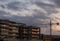 Budowa żurawia nowożytny budynek przy zmierzchem obraz royalty free