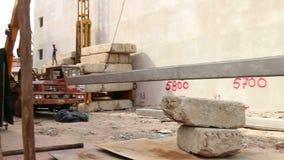 BUDOWA: Środka strzału pracownik prowadzi dźwignięcie pilon, stos betonowi/ zbiory wideo