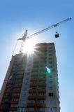 Budowa żuraw podnosi ładunek na budynku w budowie, zdjęcie stock