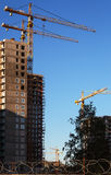 Budowa żurawie i budujący domy na niebieskiego nieba tle Zdjęcie Royalty Free