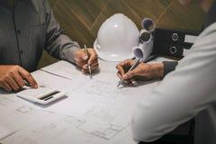 Budowa architekt lub dyskutujemy projekt podczas gdy sprawdzać informację na rysować i kreślić dla, fotografia stock