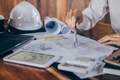 Budowa architekt lub in?ynieria wr?czamy dzia?anie na projekt inspekcji w miejsce pracy, podczas gdy sprawdza? ewidencyjnego rysu zdjęcia stock