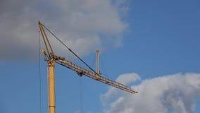 Budowa basztowy żuraw przeciw niebieskiemu niebu z ruszać się białe chmury, zbiory