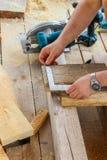 Budowa drewniany ramowy dom - mierzący prawego rozmiar deska, tnącego z saw ostrza z saw, zakończenie up obrazy stock