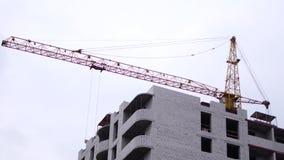 Budowa multistory, ceglany dom Montażu żuraw podnosi materiały budowlanych zbiory wideo