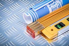 Budowa równi drewniani metrowi błękitni projekty na laskowanym metalu Fotografia Stock
