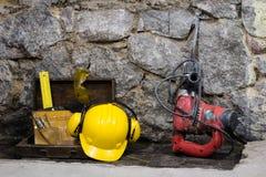 Budowa wytłacza wzory dla budować dom na kamiennej ścianie Młot, hełm i inni konieczni narzędzia dla, budowy lub rozszczepiać Fotografia Stock