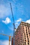 Budowa z żurawiami blisko domu przeciw niebieskiemu niebu z białymi chmurami obraz royalty free