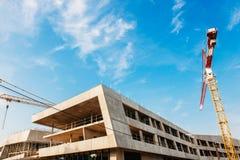 Budowa z żurawiami nad niebieskim niebem Zdjęcia Royalty Free