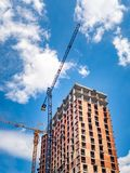 Budowa z żurawiami przeciw niebieskiemu niebu z białymi chmurami zdjęcie royalty free