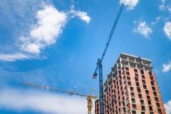 Budowa z żurawiami przeciw niebieskiemu niebu z białymi chmurami obrazy stock