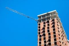 Budowa z żurawiem przeciw niebieskiemu niebu zdjęcie royalty free