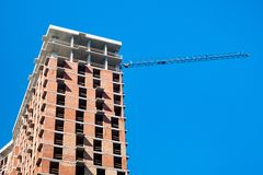 Budowa z żurawiem przeciw niebieskiemu niebu zdjęcia royalty free