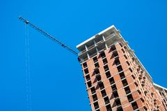 Budowa z żurawiem przeciw niebieskiemu niebu obraz stock