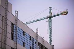 Budowa z dźwigowego whit purpurowym niebem przy zmierzchem. obrazy royalty free