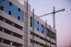 Budowa z dźwigowego whit purpurowym niebem przy zmierzchem. zdjęcia stock