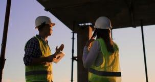 Budowniczego mężczyzna z pastylką i kobieta inspektor w białych hełmach trząść ręki przy zmierzch pozycją na dachu zdjęcie wideo