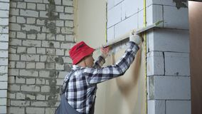 Budowniczego podesłania tynk na wietrzącej betonowy blok ścianie z budowy władcą zbiory wideo