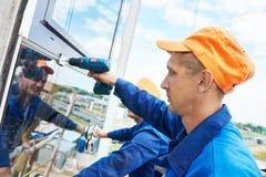 Budowniczego pracownik instaluje szklanych okno na fasadzie obrazy royalty free