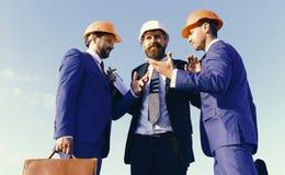 Budowniczowie dyskutuje plan i dyskutują, niebieskiego nieba tło obrazy royalty free