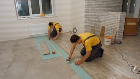 Budowniczowie instaluje laminat pod?ogi obrazy stock