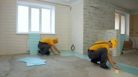Budowniczowie pracuje na pod?odze w nowym domu obrazy royalty free