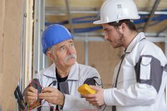 Budowniczowie używa żółtego multimeter kalibrować dom fotografia royalty free
