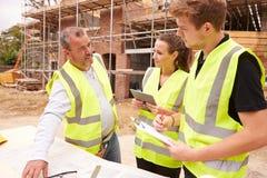 Budowniczy Dyskutuje pracę Z aplikantami Na placu budowy zdjęcia royalty free
