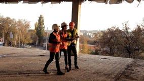 Budowniczy i żeńscy architekci oglądamy jak budowa nowy przedmiot centrum handlowe jest zbiory wideo