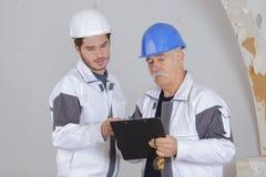 Budowniczy i inspektorska patrzeje niedokończona własność obraz royalty free