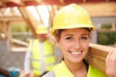 Budowniczy I kobieta aplikant przewożenia drewno Na miejscu obraz royalty free