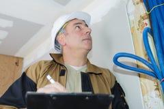 Budowniczy inspekcja sprawdza electrics zdjęcie stock