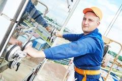 Budowniczy instaluje szklanych okno na fasadzie fotografia stock