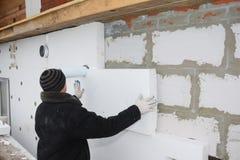 Budowniczy instaluje sztywno styrofoam izolaci deskę dla energooszczędnego fotografia stock