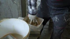 Budowniczy miesza tynk ręcznie i wypełnia przerwy w ścianie z nim zdjęcie wideo