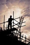 Budowniczy na rusztowanie placu budowy przy zmierzchem zdjęcia royalty free