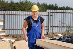 Budowniczy niesie izolującego drewnianego ściennego panelu Fotografia Stock
