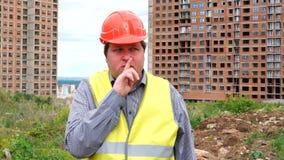 Budowniczy podnosi jego palec jego wargi na budowa placu budowym robi shushing gestowi gdy pyta dla ciszy zbiory