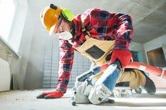 Budowniczy przy pracą tnąca betonowa podłoga dla depeszować diamentową rozpruwanie maszyną obrazy stock